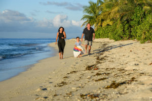 Father, mother and daughter run on the beach