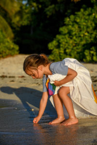 Young girl draws in the sand on the beach