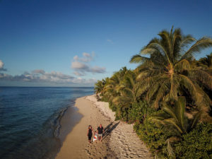An aerial view of the family strolling on the beach of Vomo Island