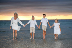 Family holding hands and walking in the Fijian sea
