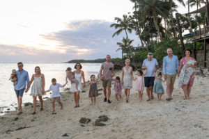 Group shot of the whole family walking together hands in hands on the beach of the Shangri La in Fiji at sunset.