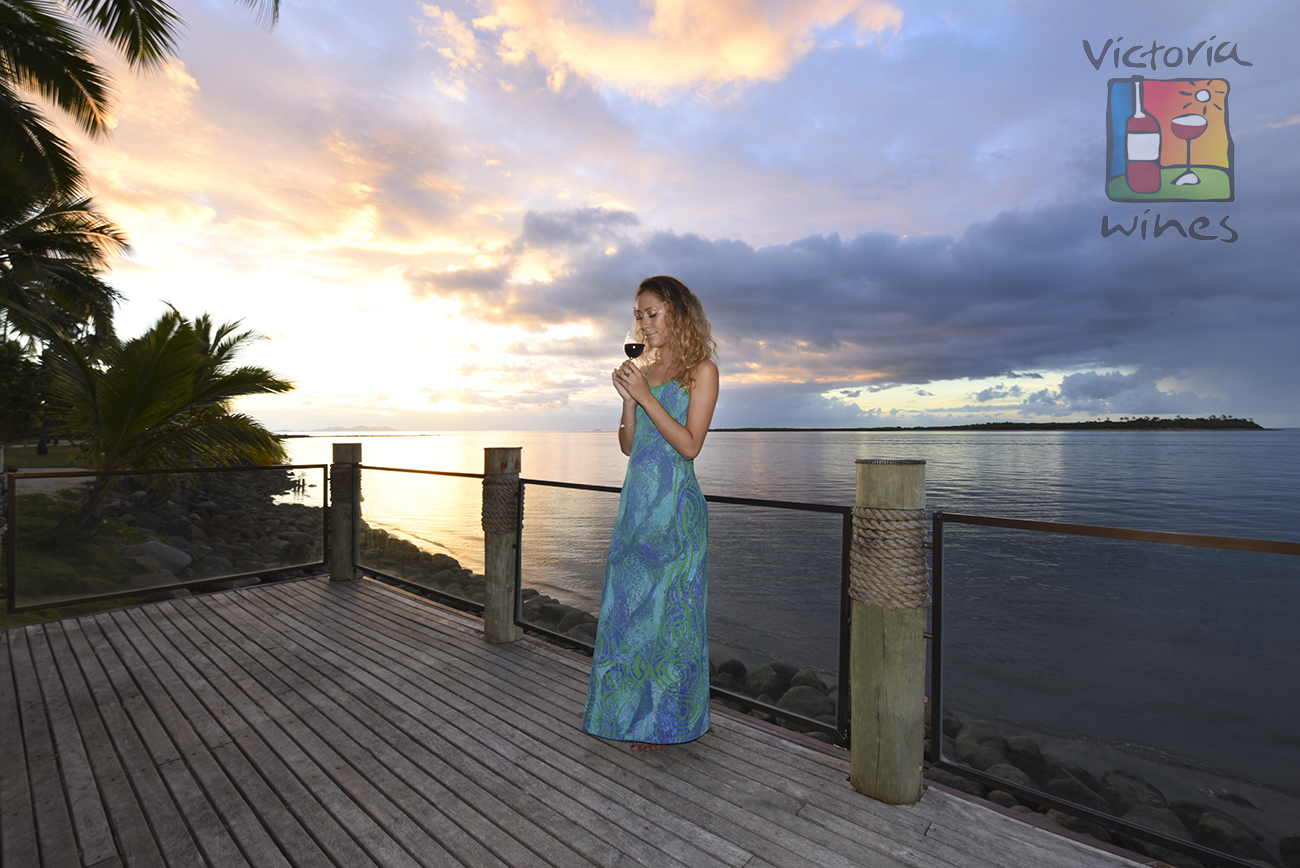 On a terrace a beautiful woman smelling the flavor of a glass of red wine in front of a impressive sunset in Fiji logo