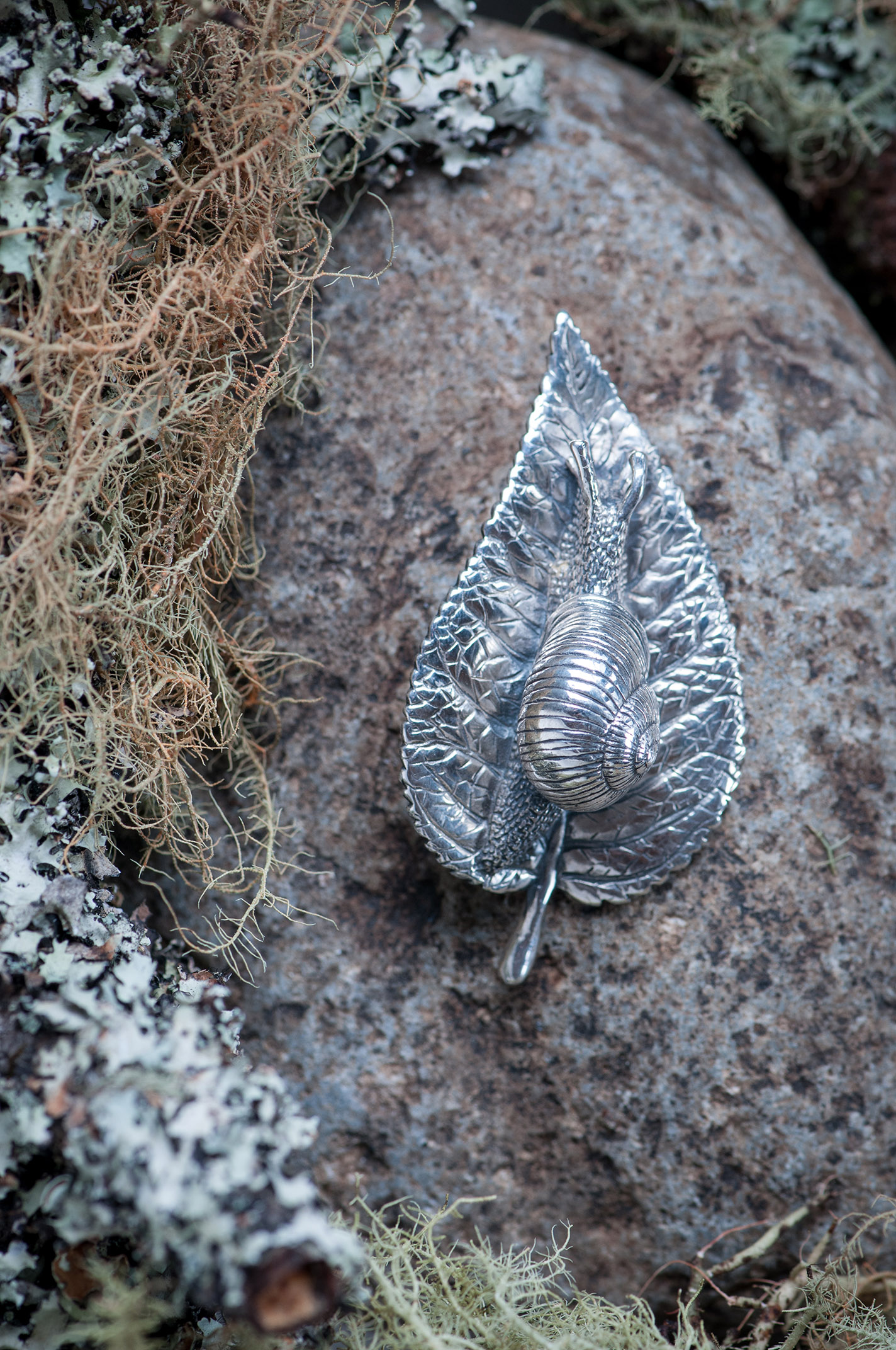 Silver snail-on-leaf brooch Product photography Anais Chaine professional Auckland photographer for Auckland museum www.anaischaine.com