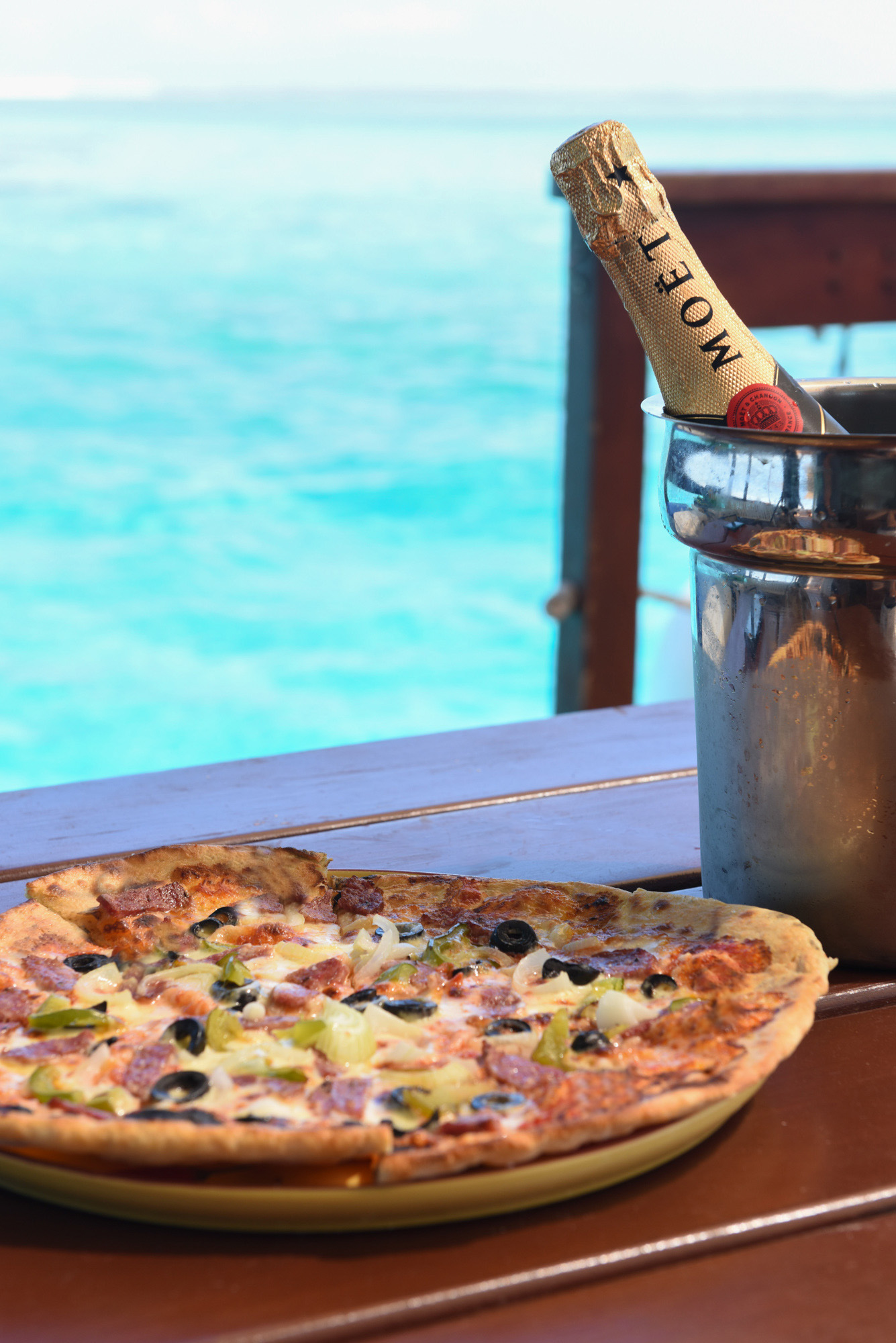 Composition with home made pizza oven and a bottle of champagne in ice pot in front of the blue sea