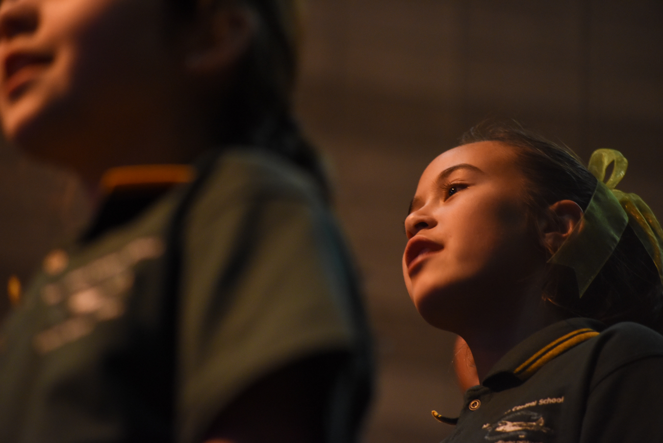 Low-angle shot of a little girl singing in a choral from the green team