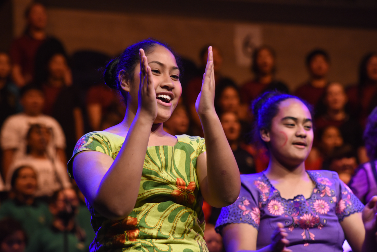 Half-cropped of a student singing and dancing and clapping in her hand wearing traditional pacific island clothes