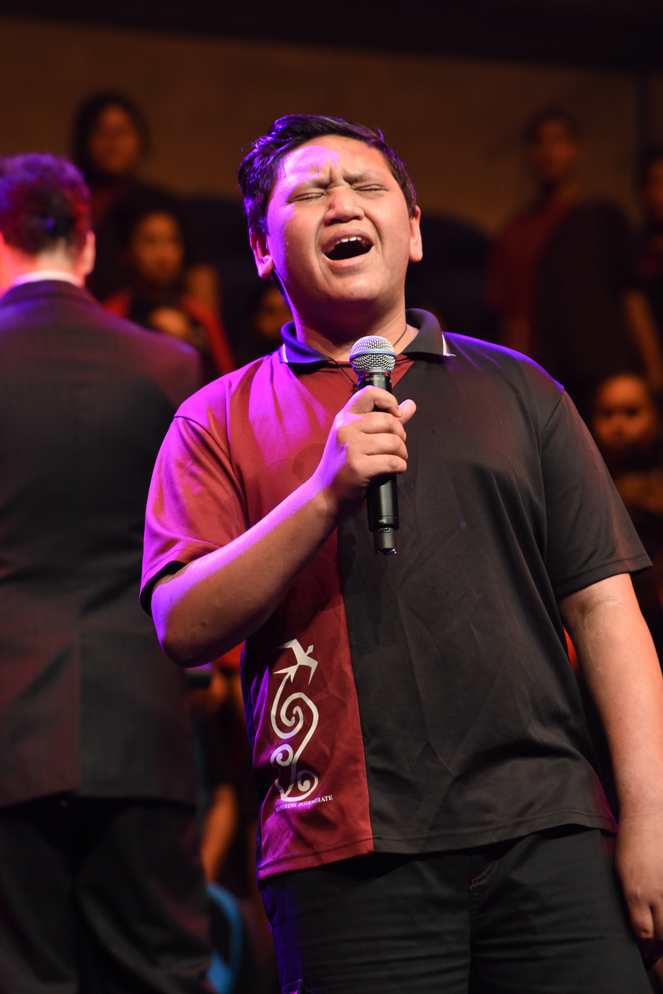 A boy singing intensely at the Vodafone Event Centre in the stage