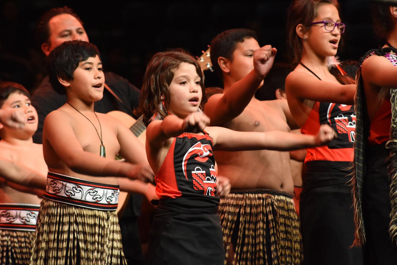 Maori students singing and dancing synchronized traditional maori dance
