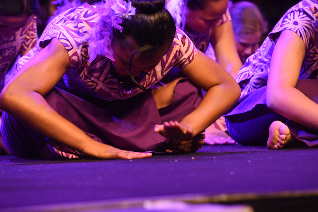 Close-up of girls dancing seating on the floor with purple dress