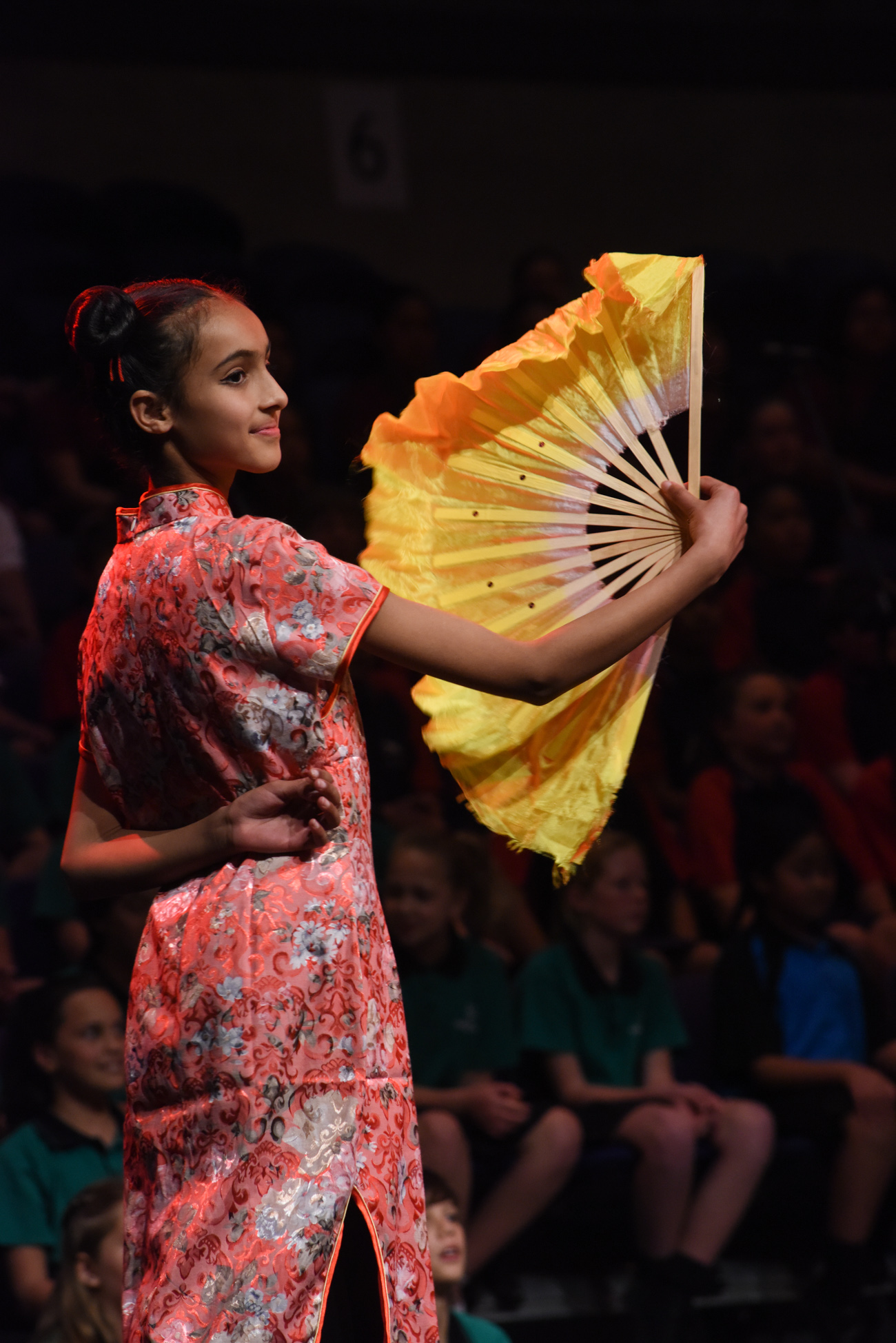 A girl dancing gracefully with a yellow fan Vodafone Event Centre