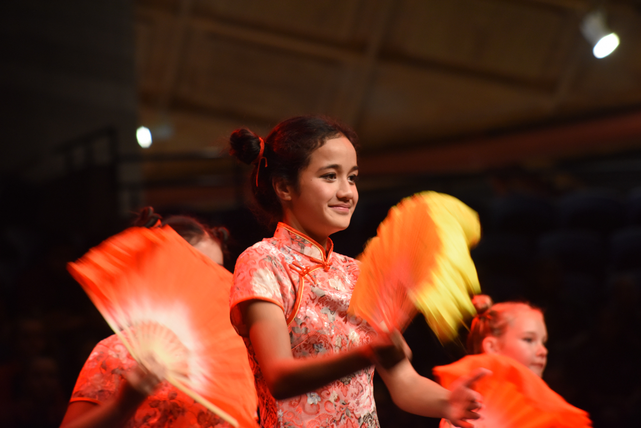 A girl dancing gracefully with a yellow fan traditional chinese dance