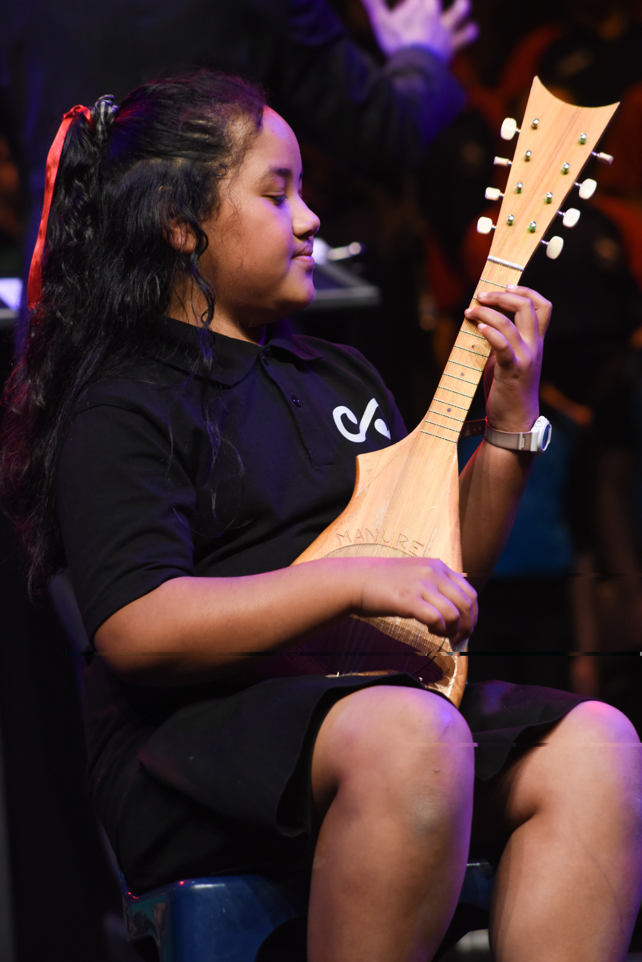 A young girl playing a traditional ukulele of Pacific Islands