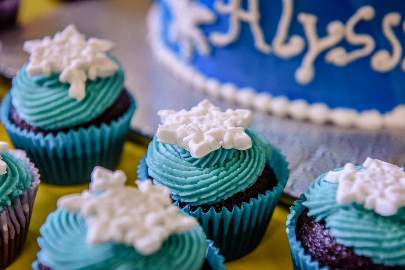 Blue frozen cup cake and birthday cake with Alyssa written as icing on the big cake