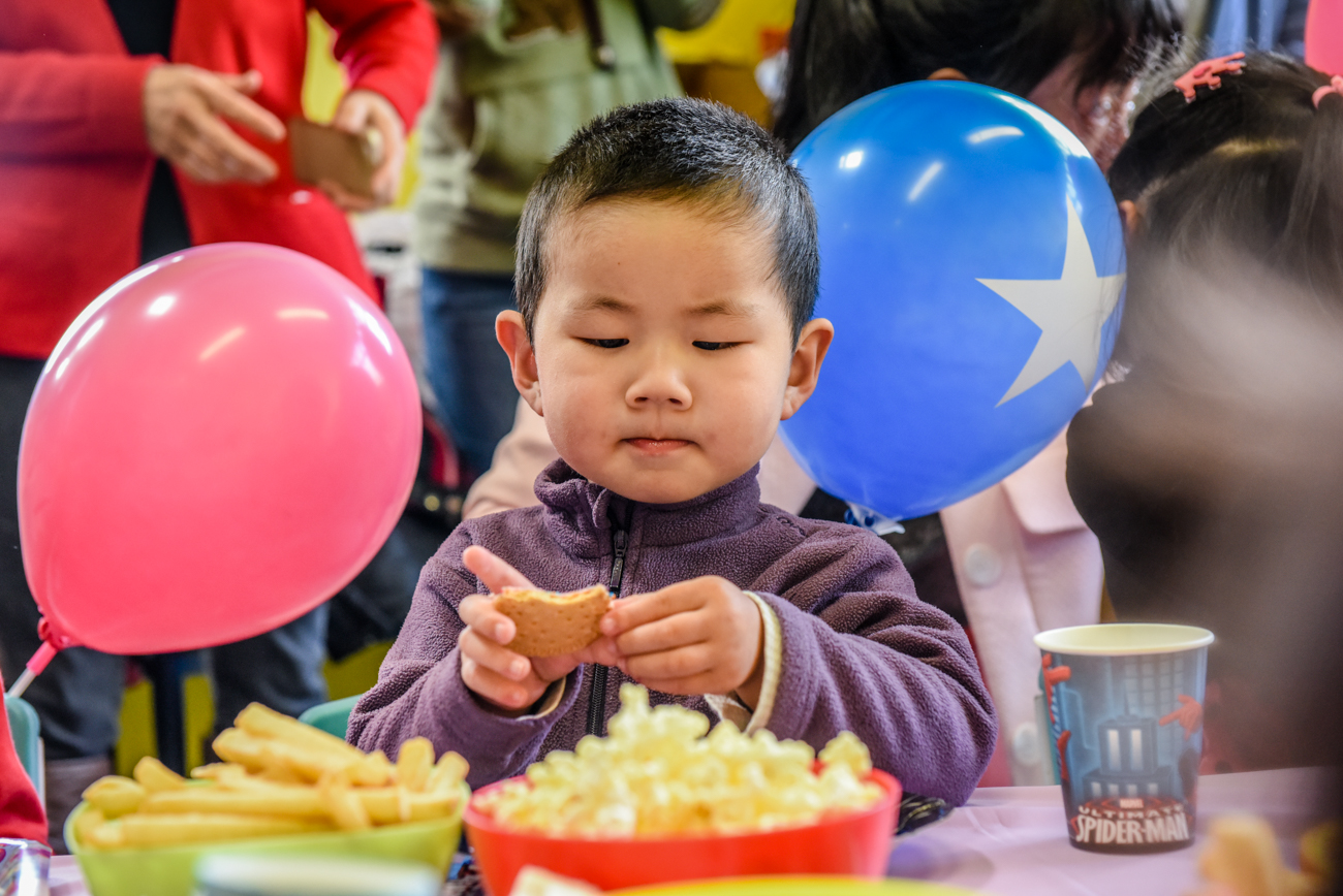 young asian boy eating a cake