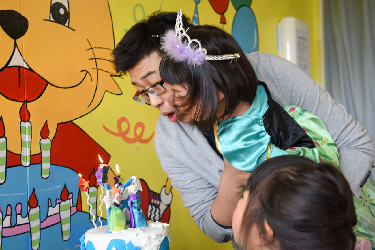Daughter is her father's arms blowing off er candles on the birthday cake