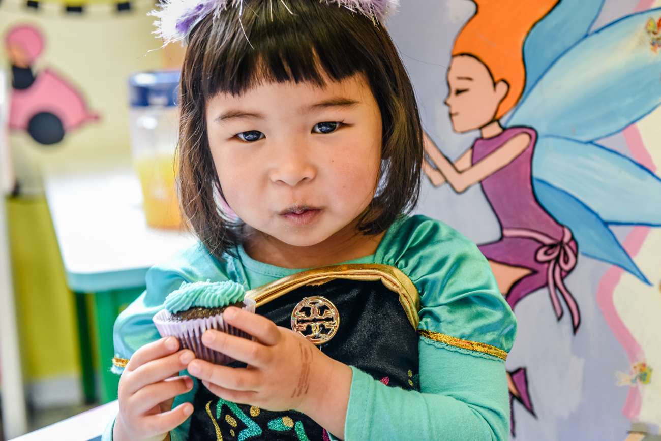 Young chinese girl girl eating her blue cup cake by Anais Photography auckland