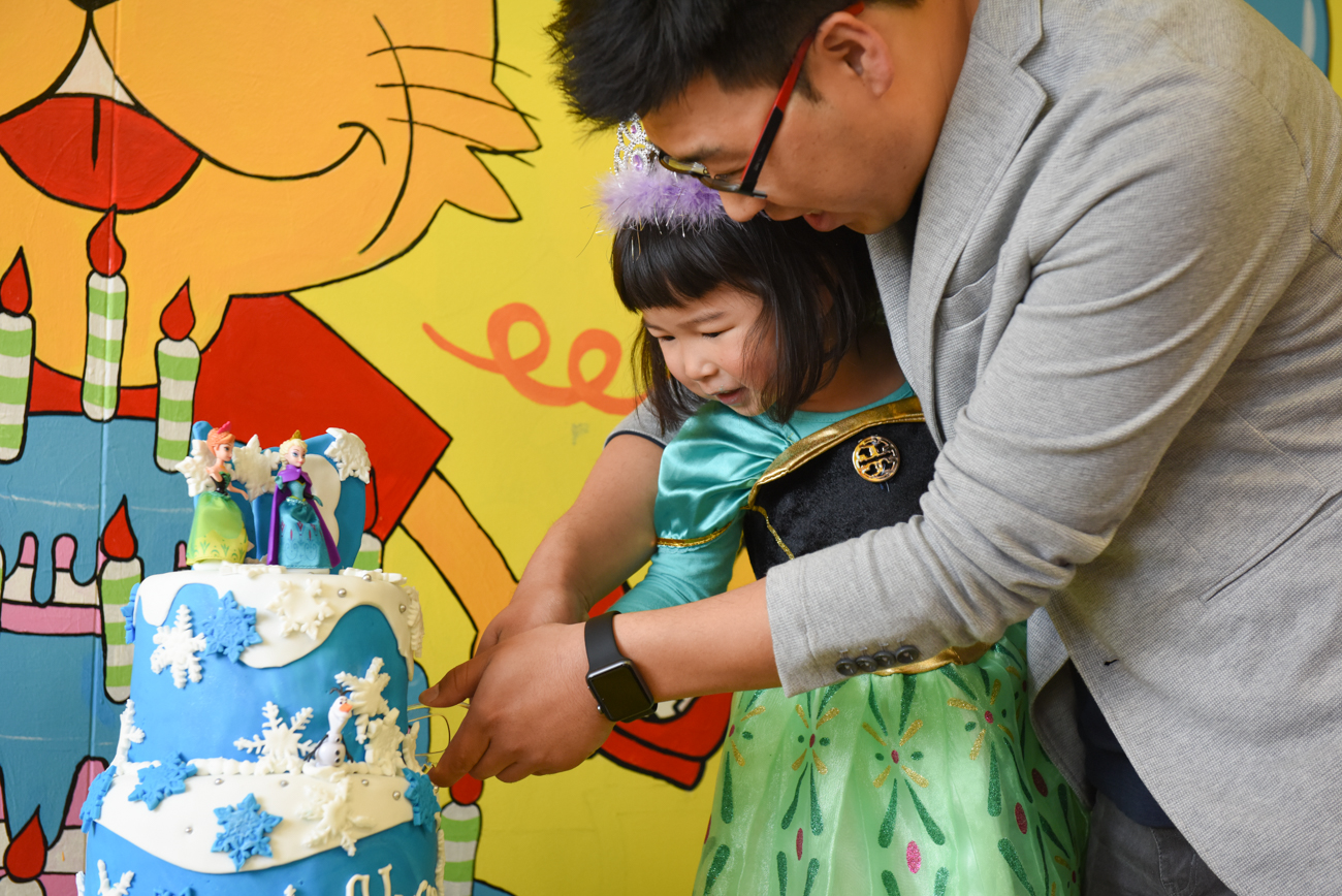 young girl cutting the cake with her father