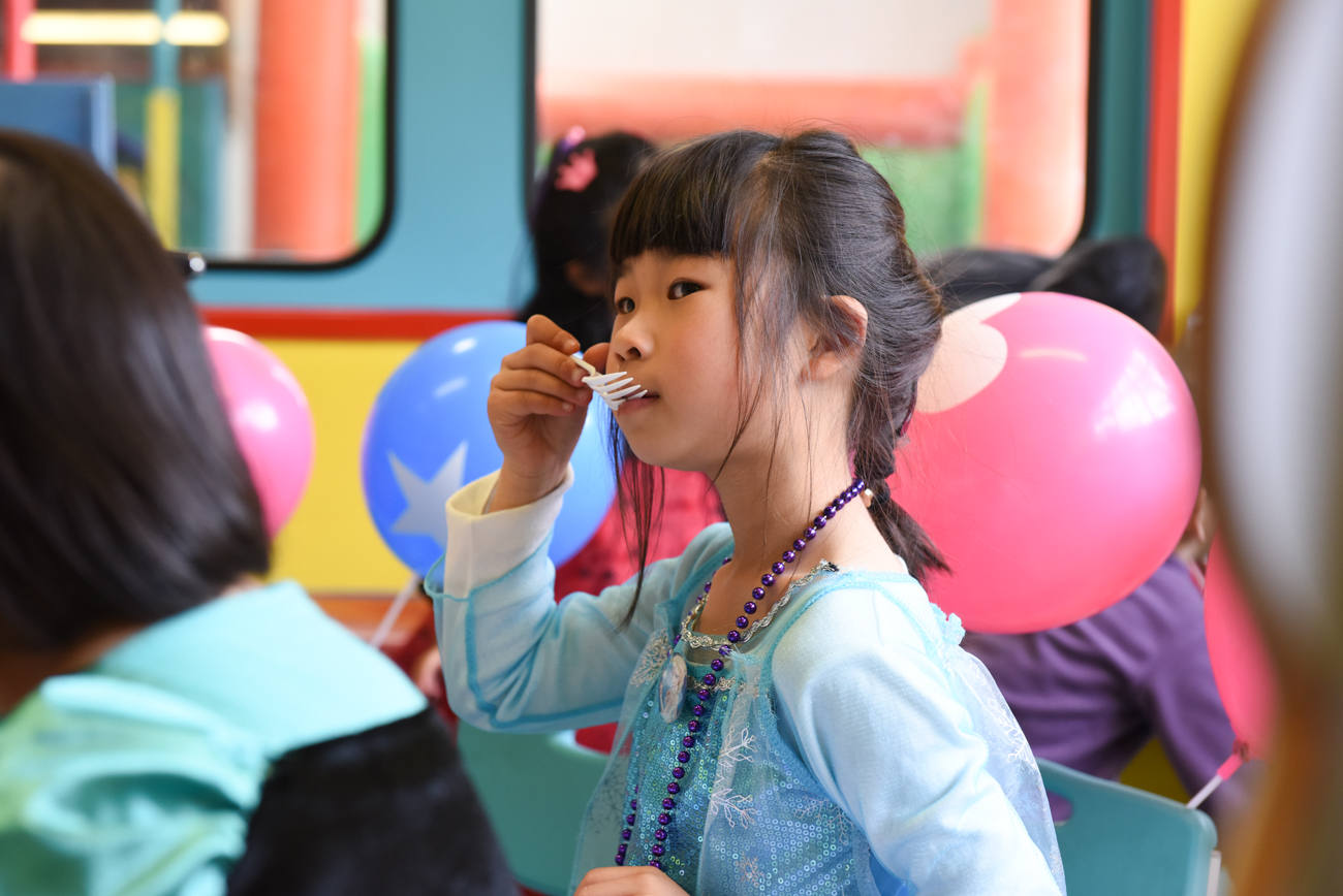 young girl with a fork in her mouth