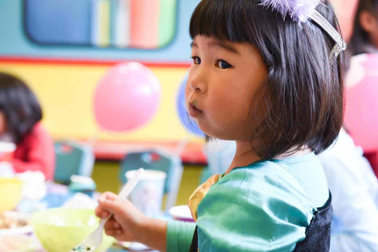 little girl chewing her birthday cake