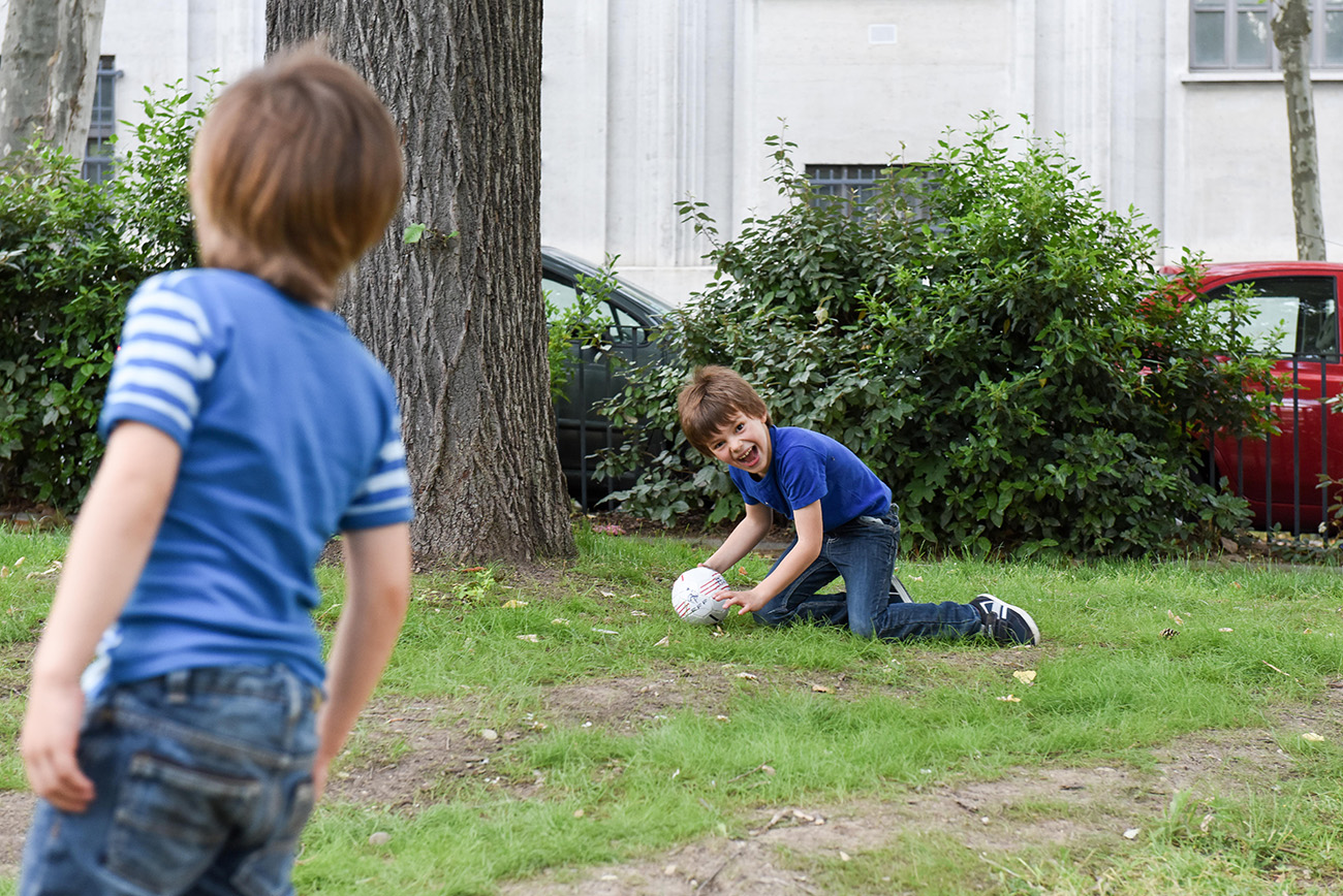 grand frere qui arrete le but en jouant au foot dans le parc