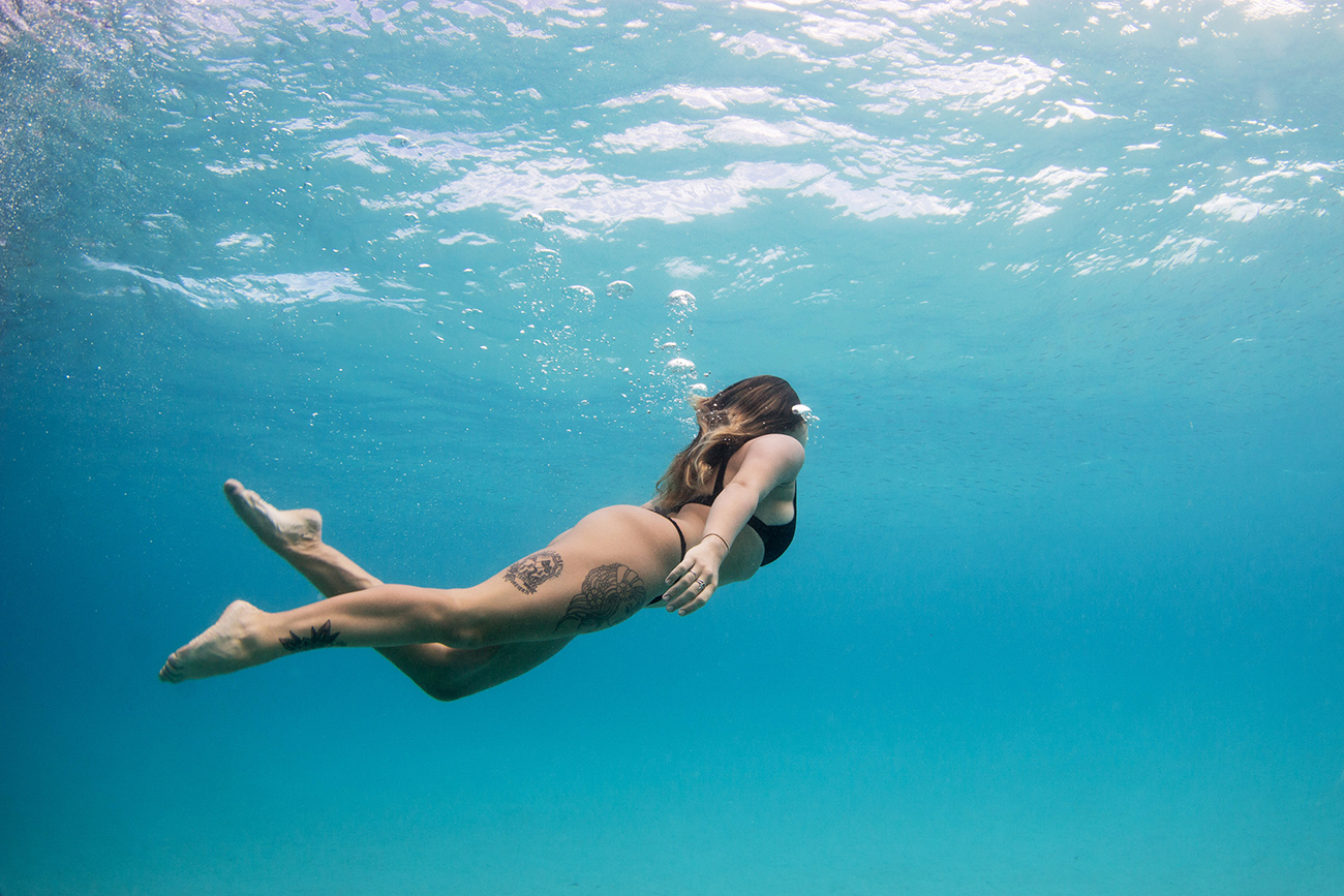 Woman with tattoos swimming underwater