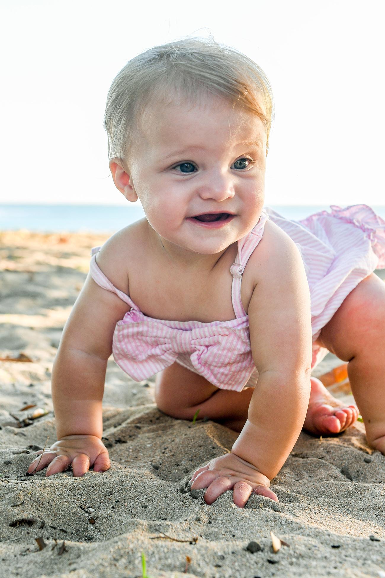 Baby crawls on sandy beach in Family photoshoot at Natadola beach Fiji