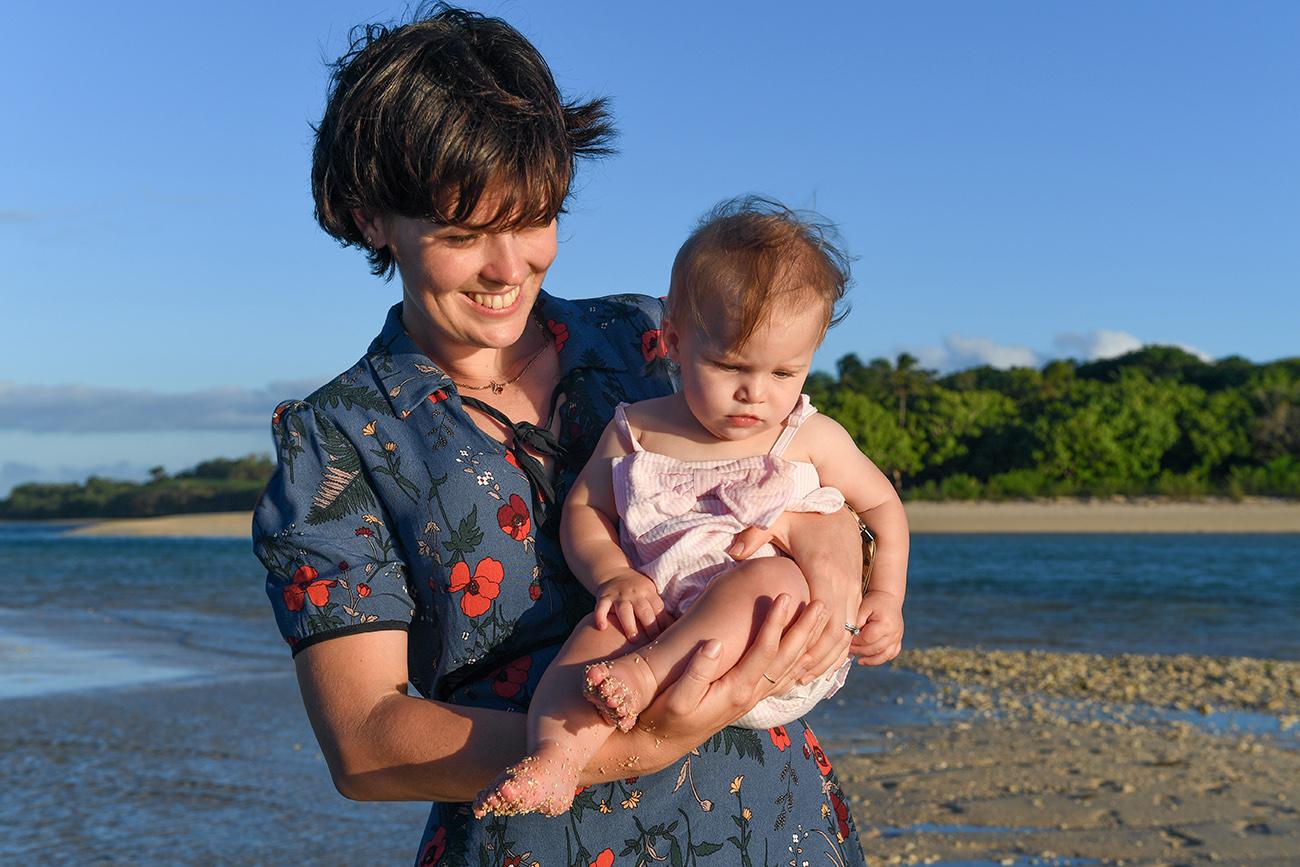 Mom cuddles daughter by Natadola beach Fiji
