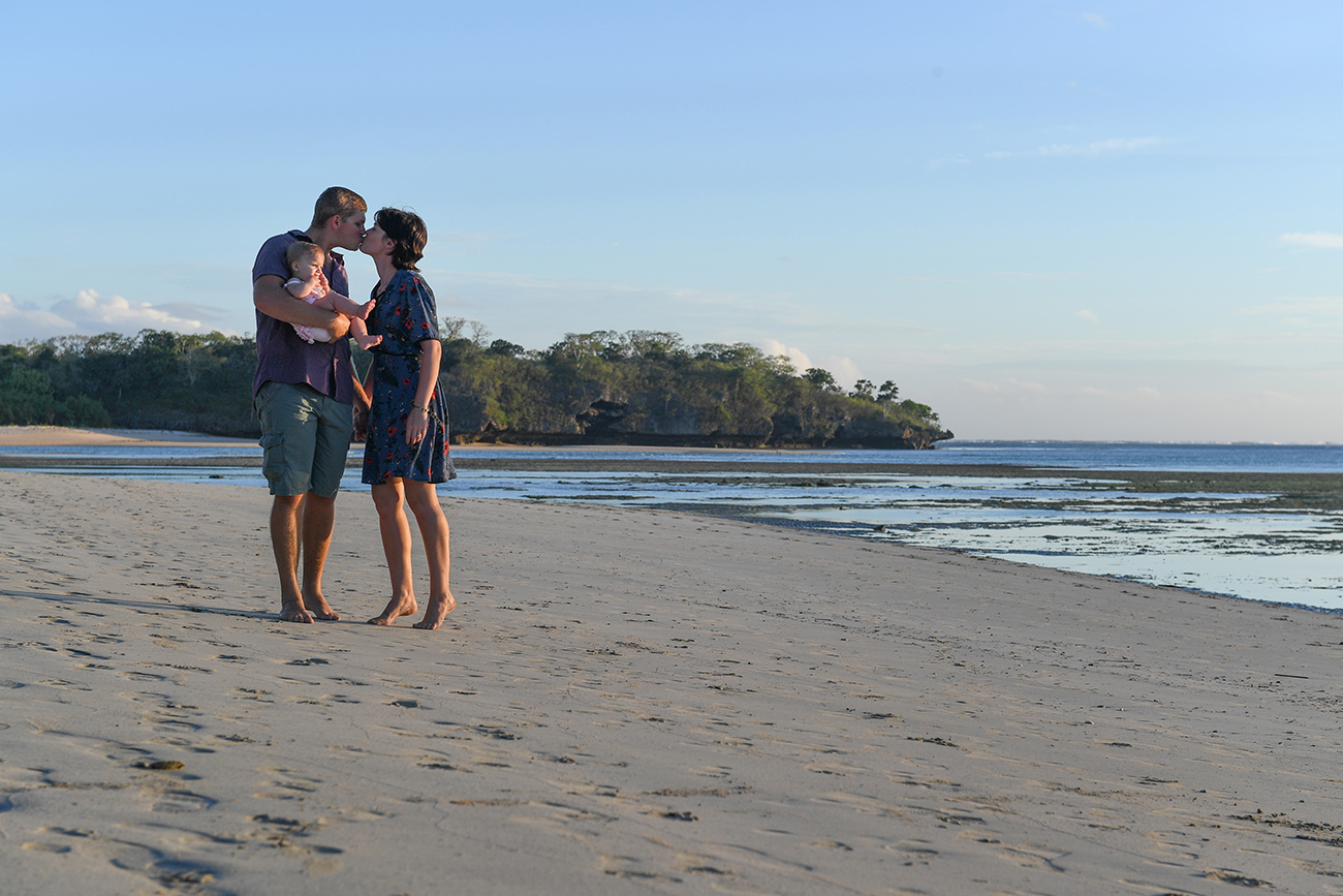 Mom and dad kiss on the beach at Natadola beach Coral Coast Fiji