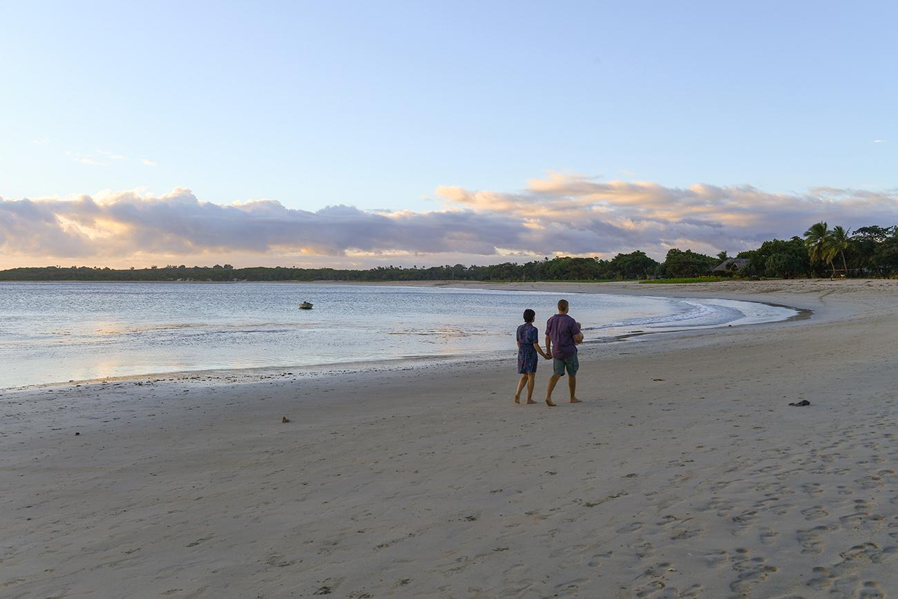 Mom dad and daughter walk down the sandy beach of Natadola in Fiji