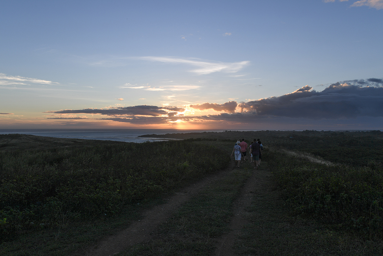 Family walking down a deserted road up a hill in Fiji coral coast at sunset