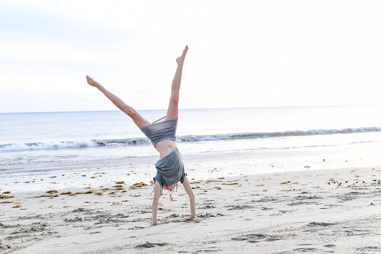 Young girl does cartwheels on the beach
