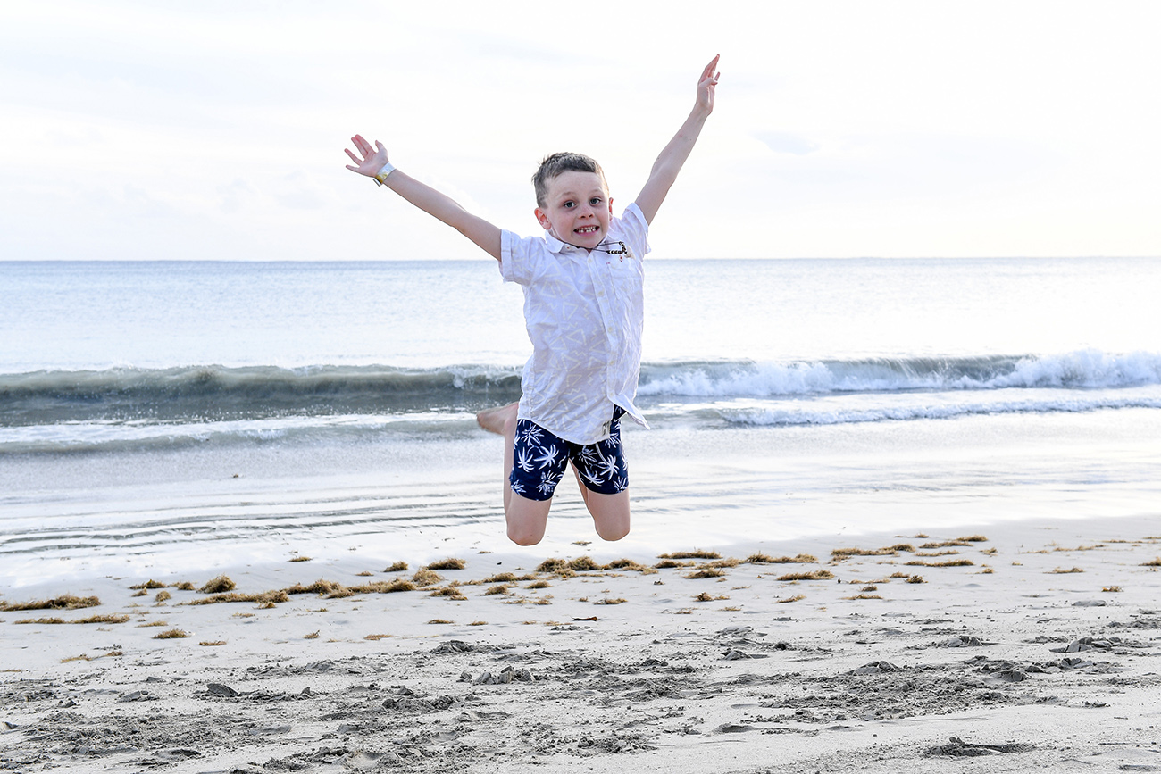 Boy jumps on the beach in Fiji sunset