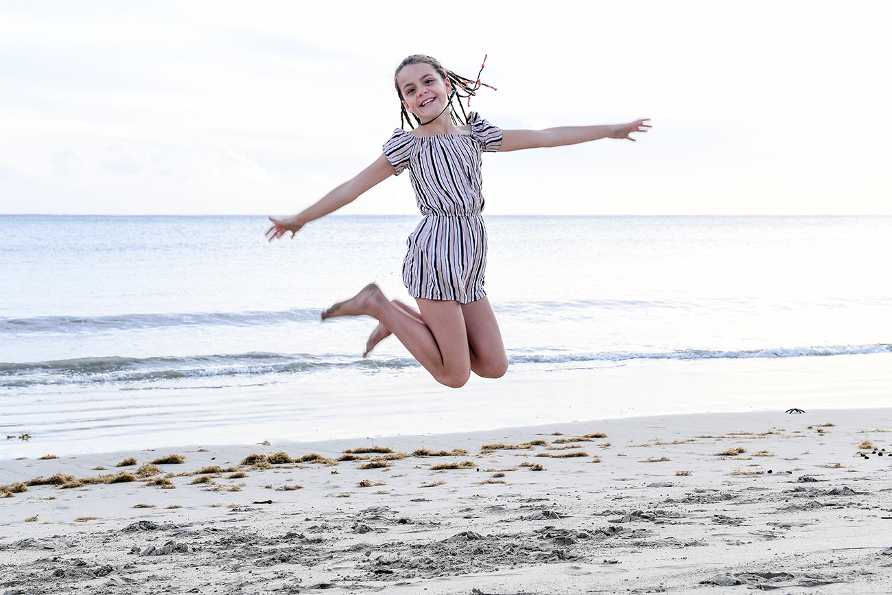Young girl with braids jumps on the beach in Fiji sunset