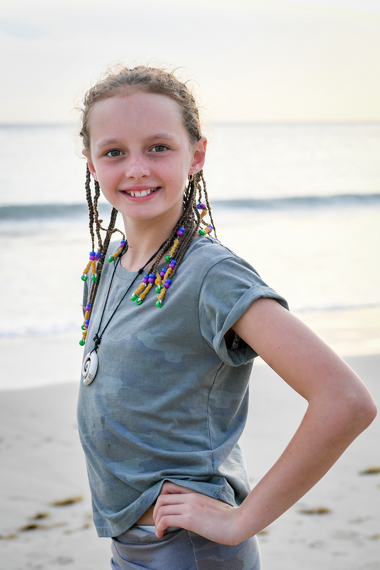 Cute young girl smiles at the camera on Fiji beach
