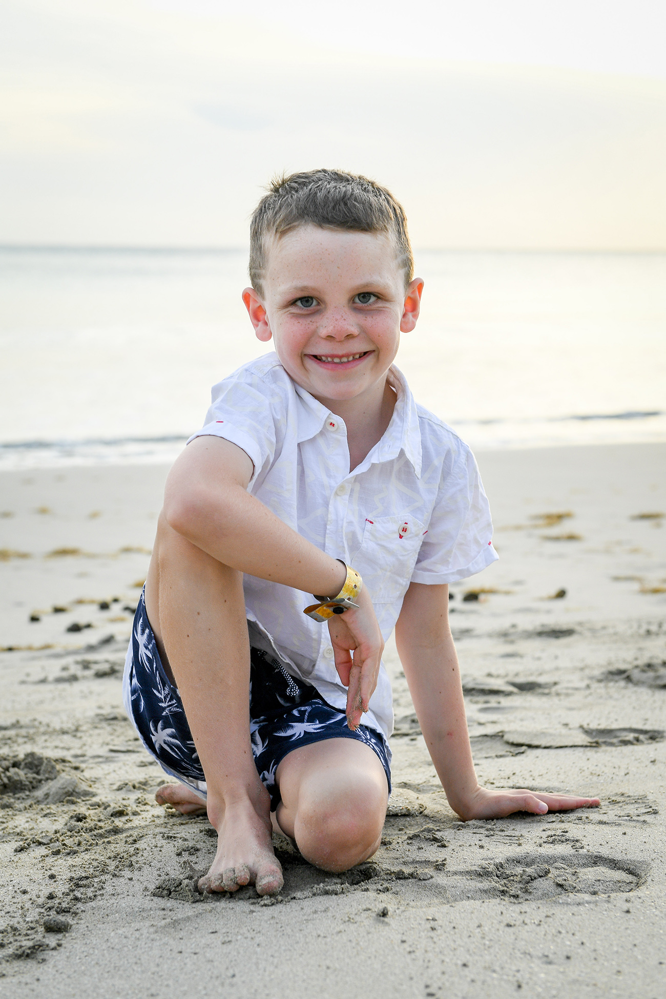 Young boy seated on the beach in Fiji