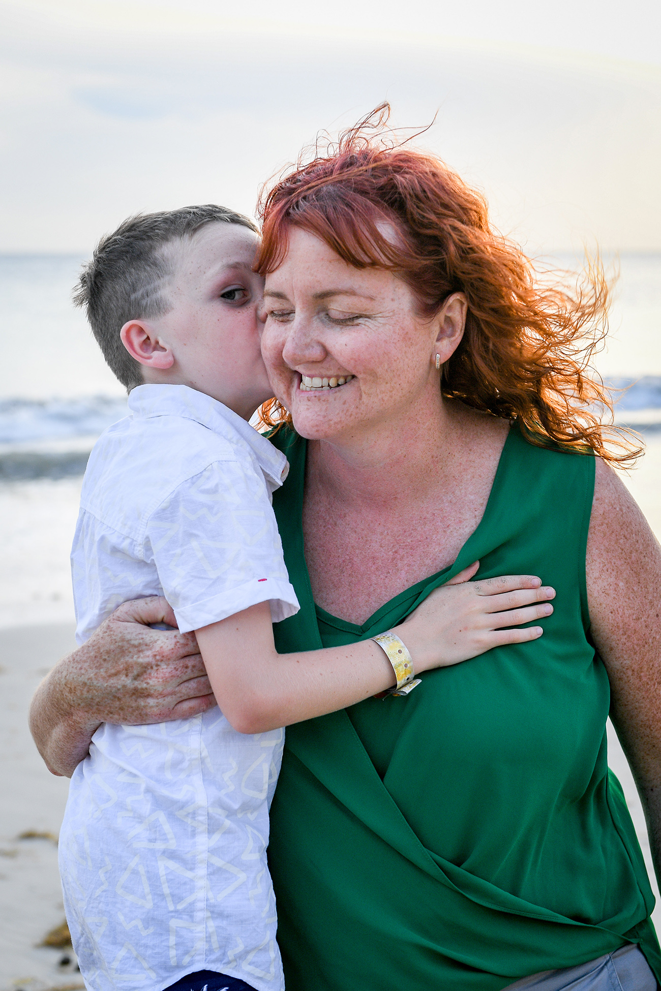 son kisses Red haired mum on beach in Fiji