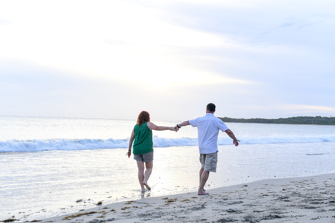 Husband and wife hold hands while walking on the beach in Fiji photography