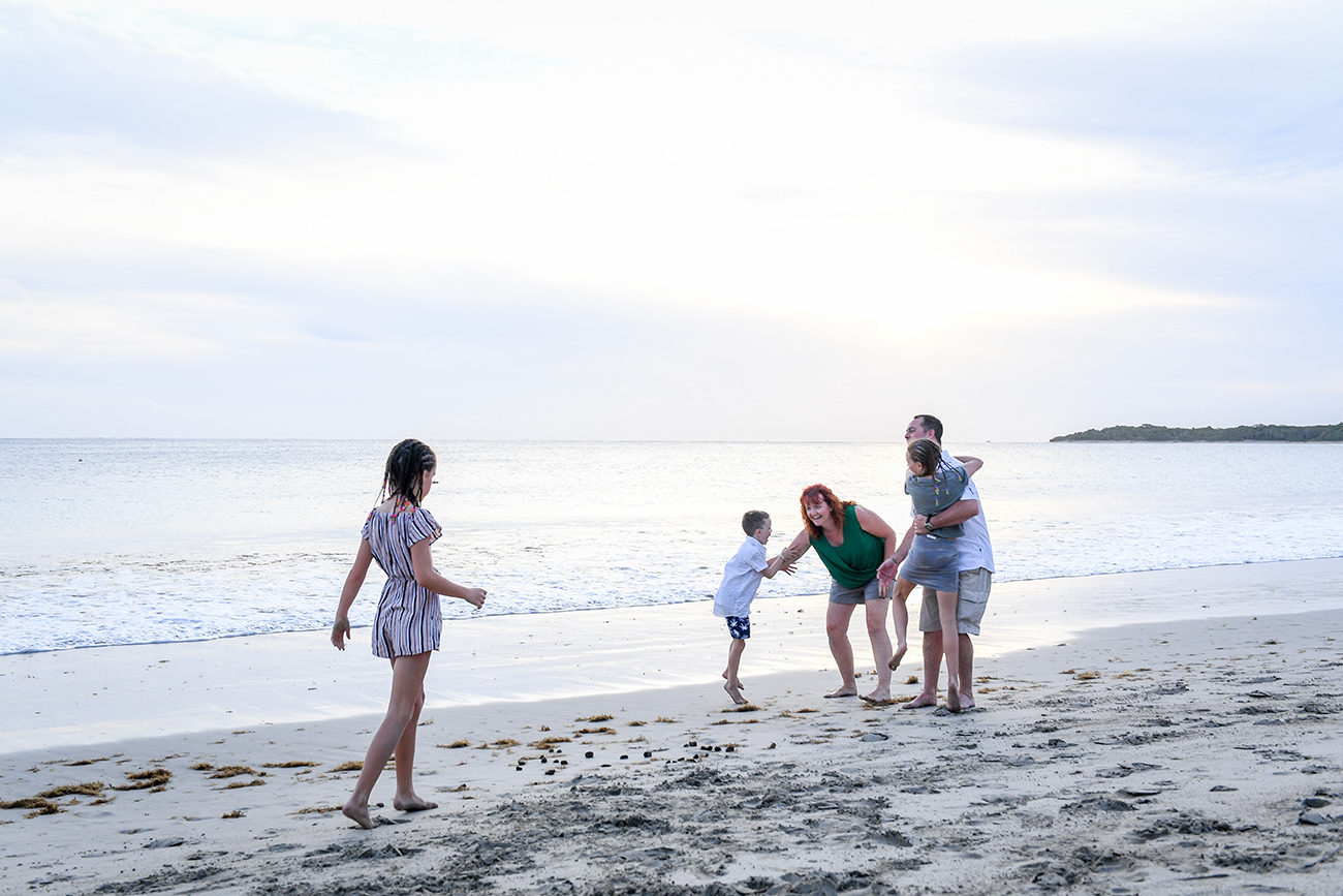 Wideshot of family hugging and playing on the beach in Fiji family photoshoot
