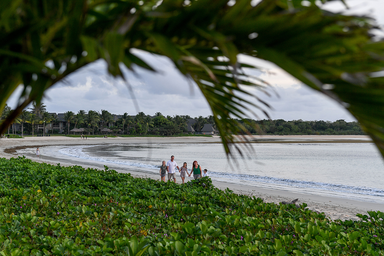 Wideshot of family with palm trees in the foreground on the Natadola beach Fiji