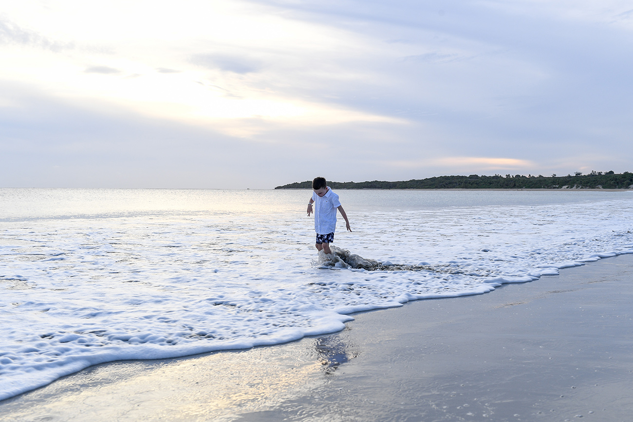 Young boy strolls in the ocean at sunset in Natadola Fiji