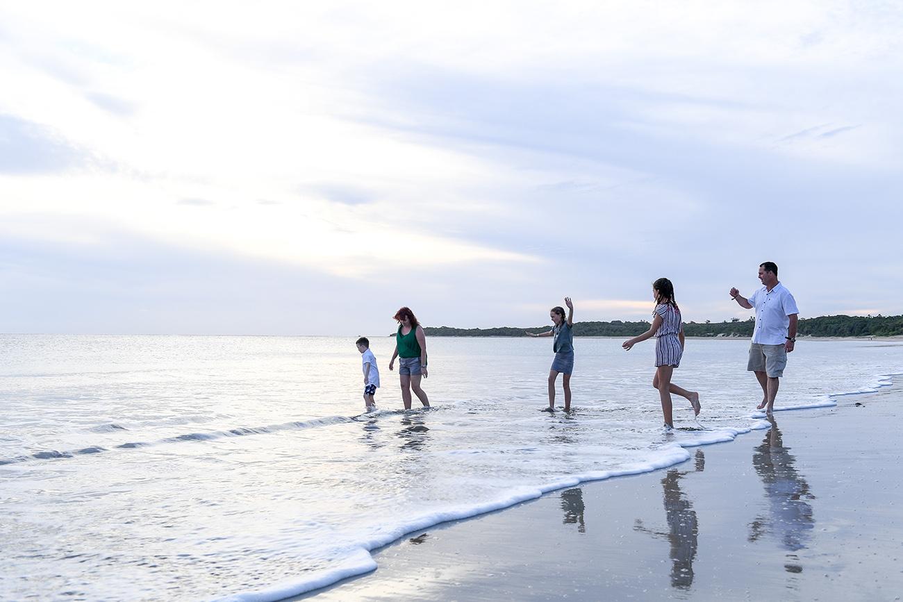 Silhouette photo of family walking in the ocean on Natadola beach Fiji