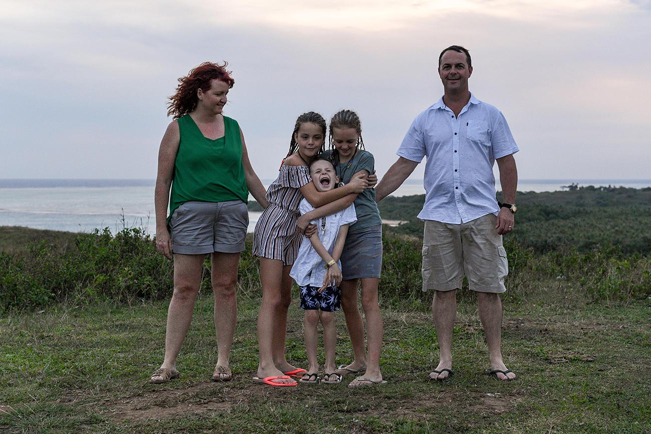 Family hug in Fiji countryside for family photoshoot