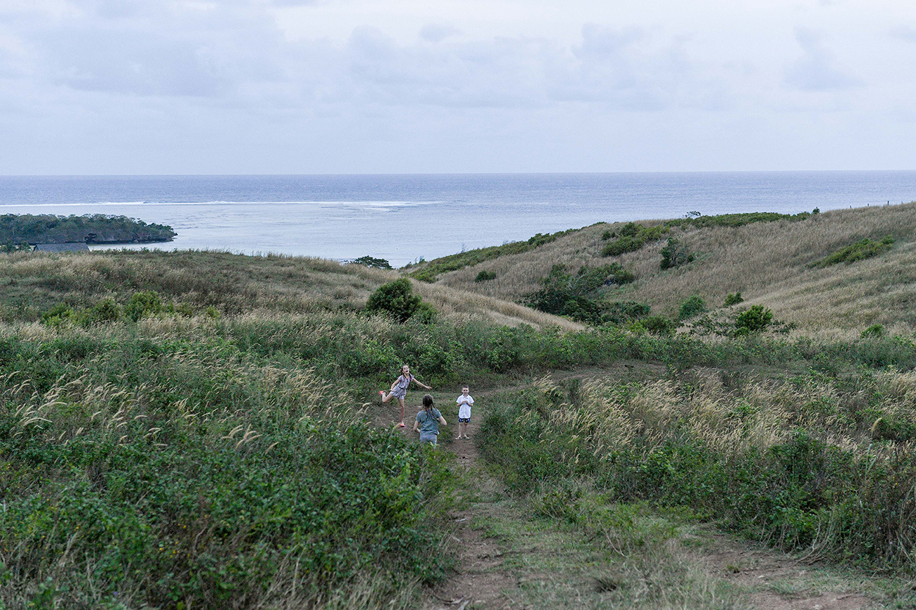 Stunning landscape photo of brothers and sisters playing in Fiji countryside against ocean in Natadola Fiji