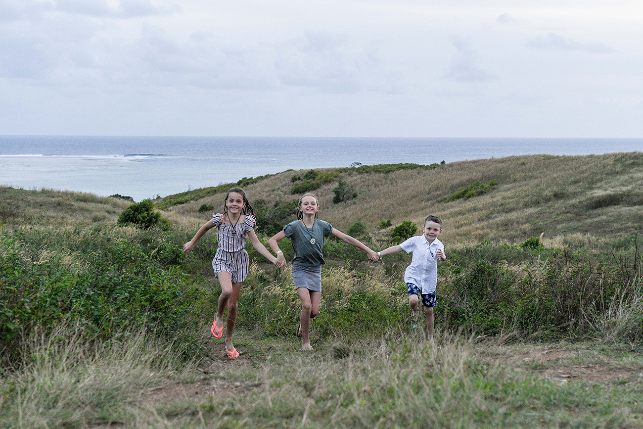Cute brother and sister run in the countryside against ocean and sunset in Fiji family photoshoot