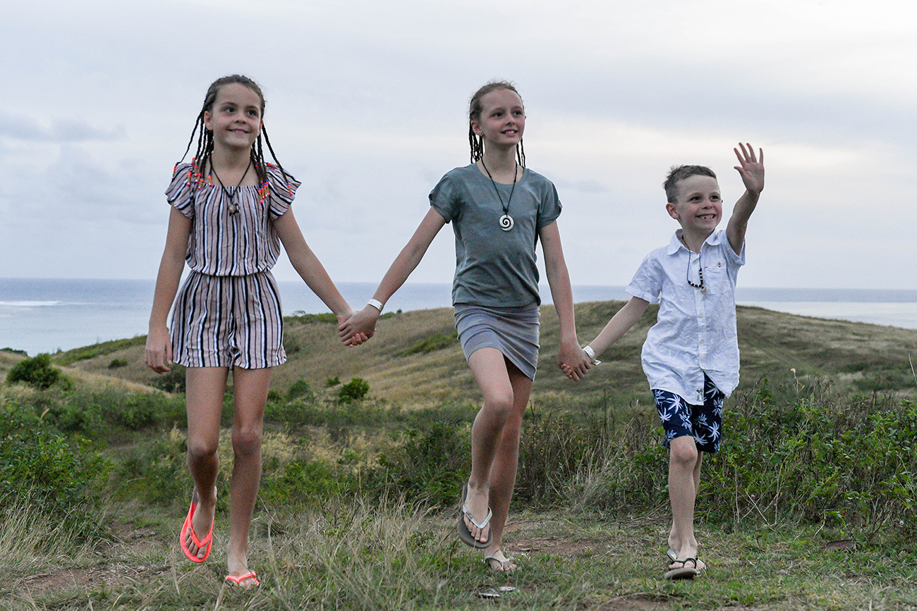 Cute brother and sisters walking in countryside at Natadola beach