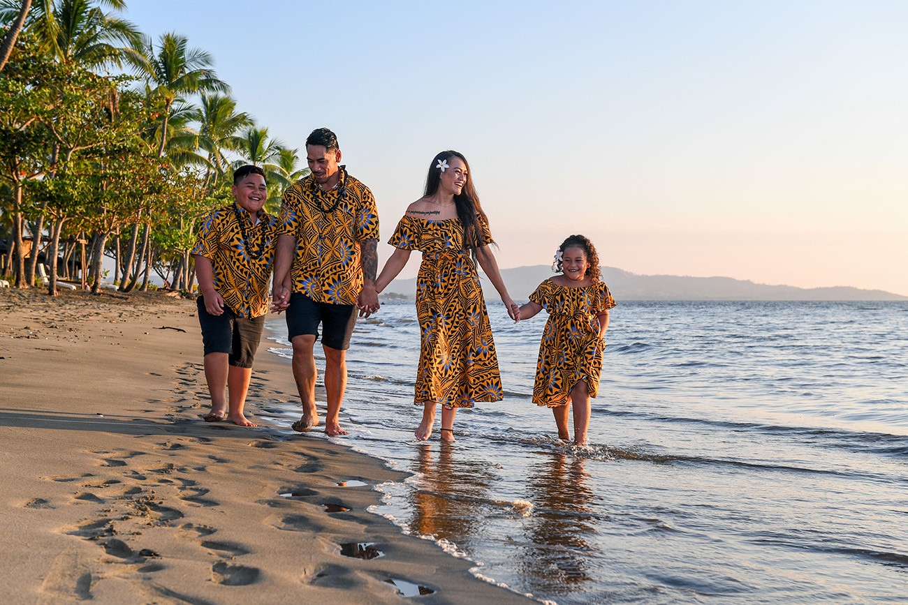 The family holds hands as they stroll into the sea at Fiji