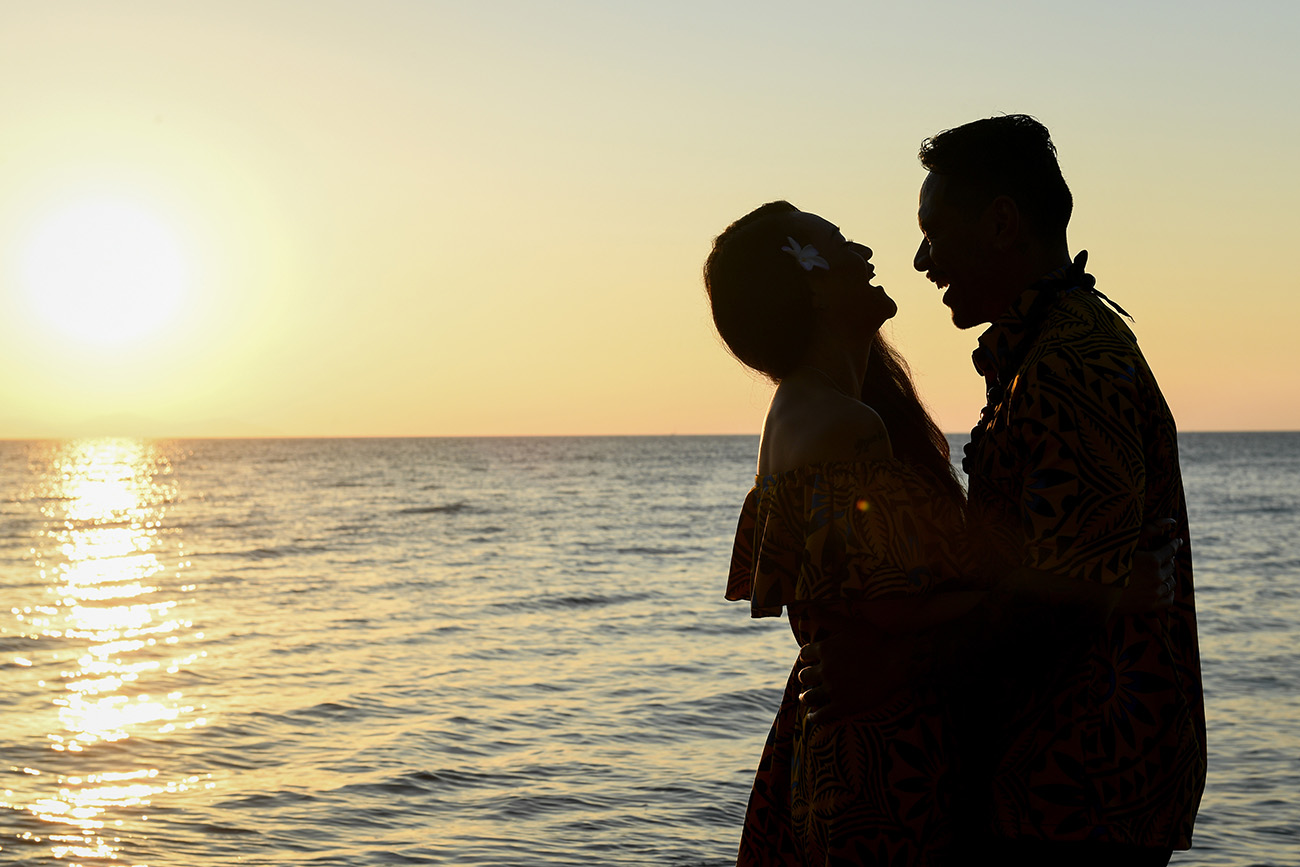 Mother and father are silhouetted as they laugh with the golden sunset behind them