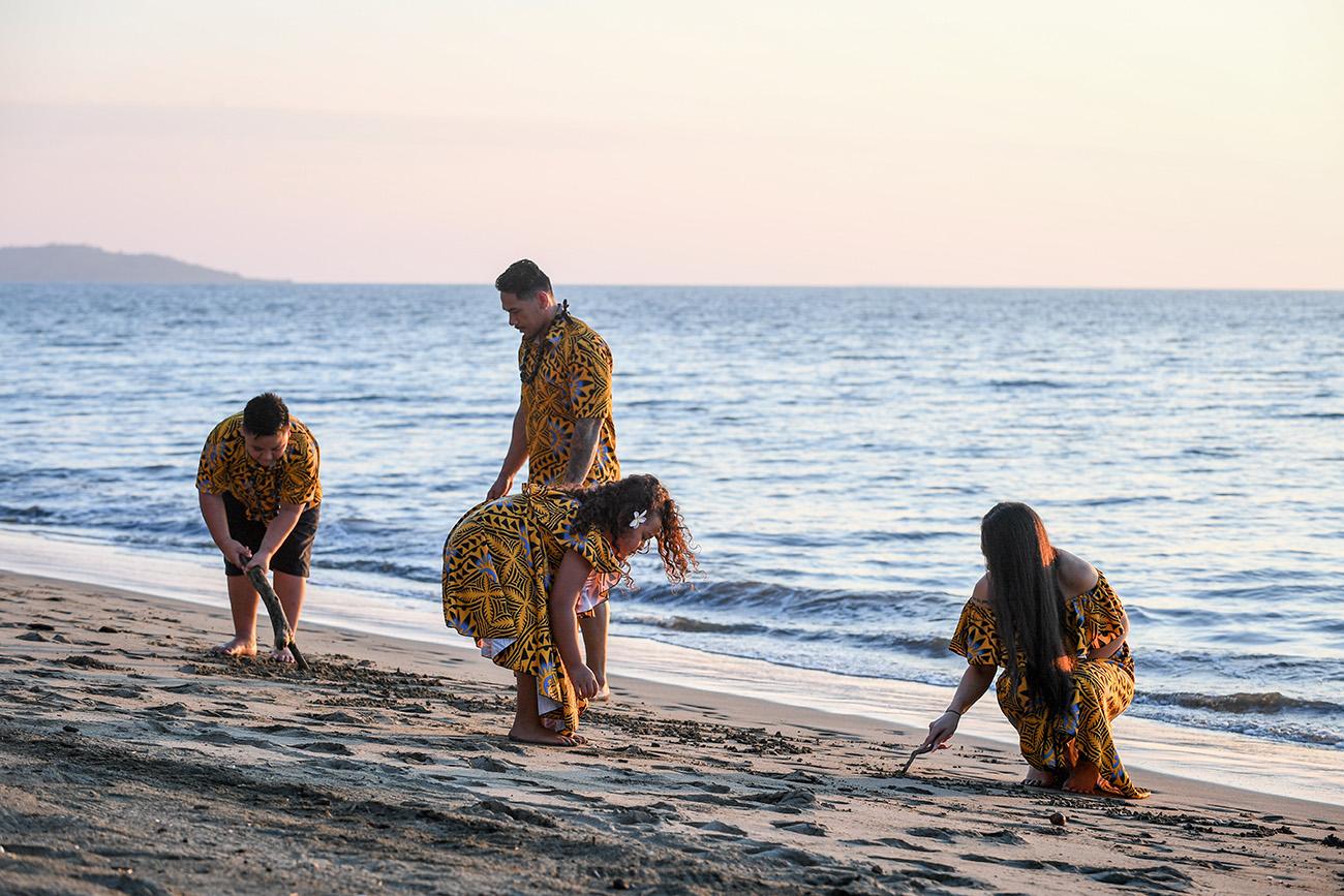 The family collects seashells on the beach at Double Tree Hilton Fiji