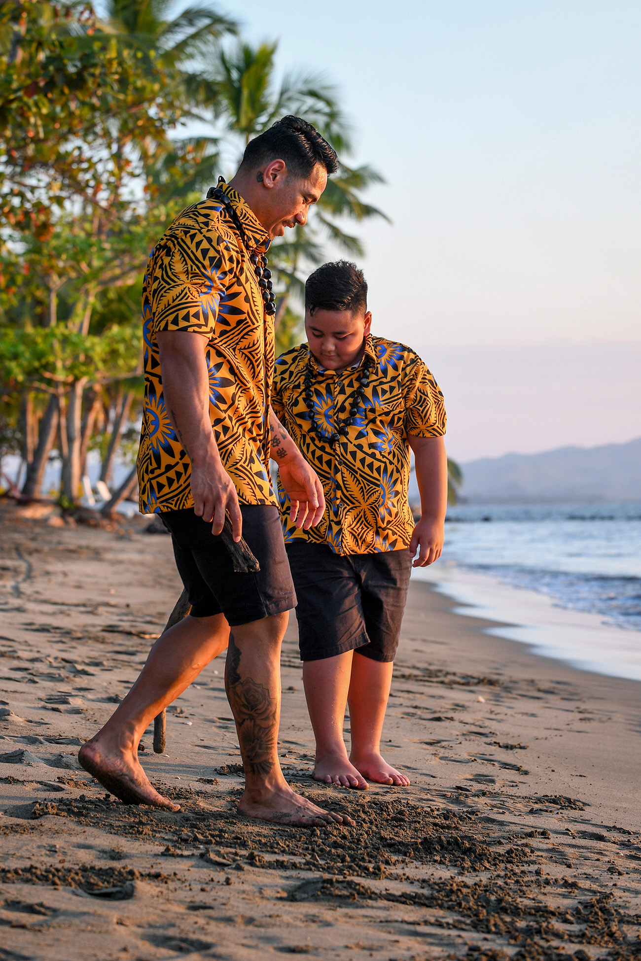 Father and son with muddy feet play with the sand on the beach