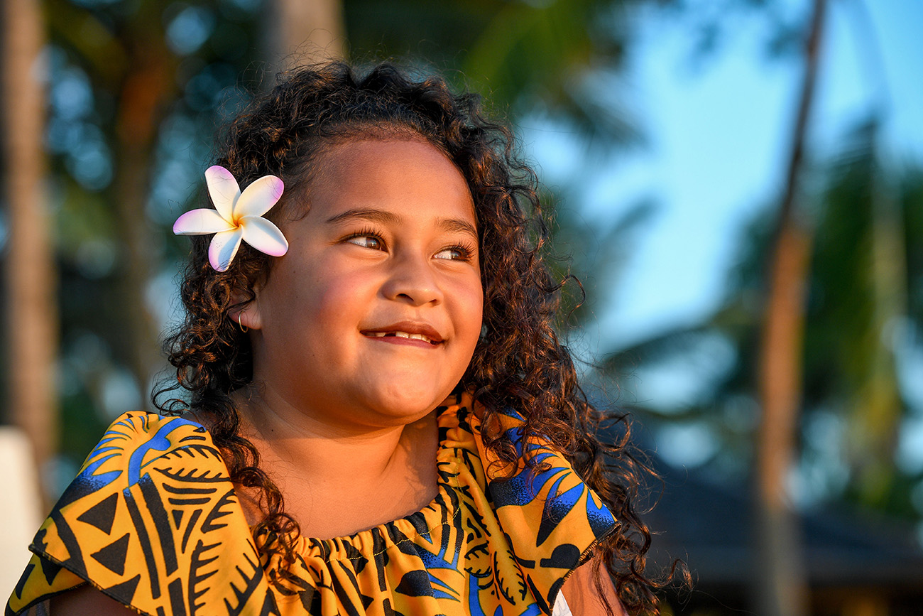 Sun-kissed daughter stares into the sea with frangipani flower in her hair
